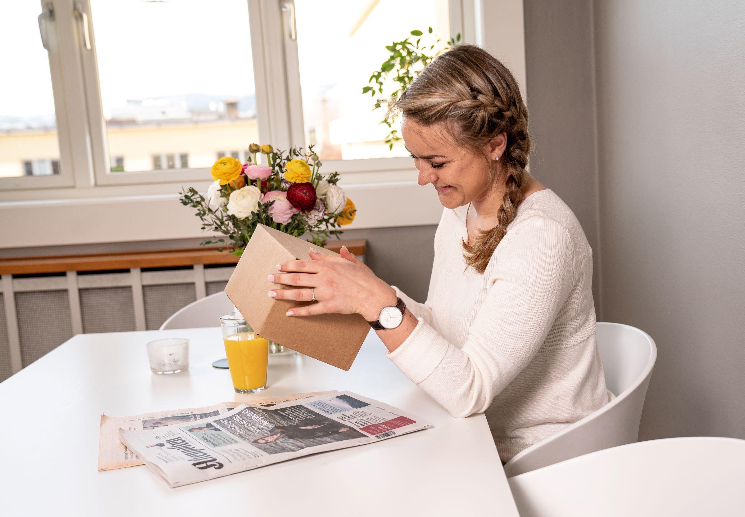 Pakke og avis ved frokostbordet